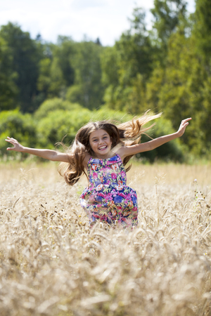 Portrait of a beautiful brunette little girl on the background of wheat field