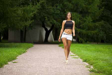 Portrait of young brunette woman in white short walking in summer park, outdoors Stock Photo