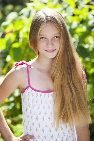 pretty eyes: Portrait of a beautiful young blonde little girl on the background of summer park