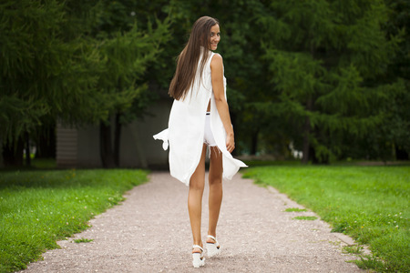 Portrait in full growth, young beautiful brunette woman in white dress walking on the summer park, outdoors