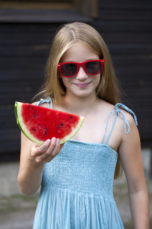 blonde little girl: Portrait of a young blonde little girl with watermelon, summer outdoor Stock Photo
