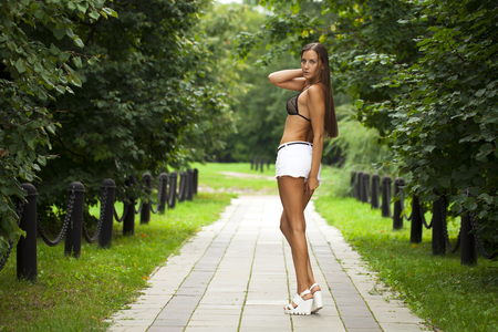 Portrait of young brunette woman in white short walking in summer park Stock Photo