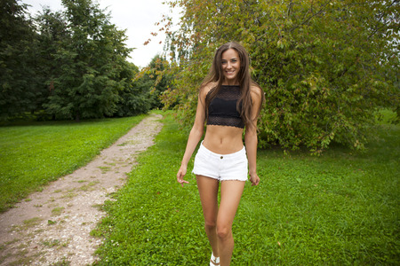 Portrait of young brunette woman in white short, summer park outdoors