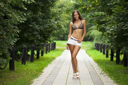 Portrait of young brunette woman in white short in summer park