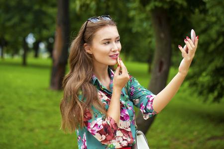 visage: Assistant lipstick beautiful young brunette woman close up, summer outdoors