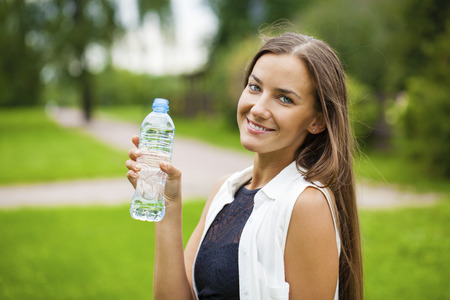 dark haired woman: Portrait of young beautiful dark haired woman drinking water at summer green park