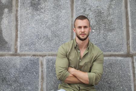 Retrato de un hombre serio en una camisa verde que presenta en un fondo de la pared de piedra