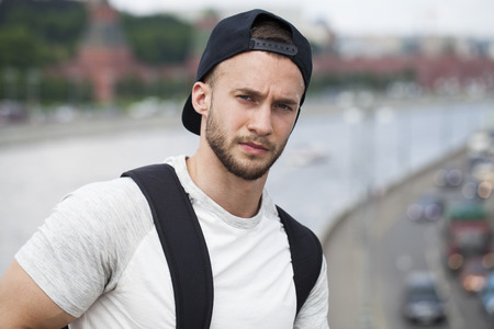 A young and attractive man in black cap