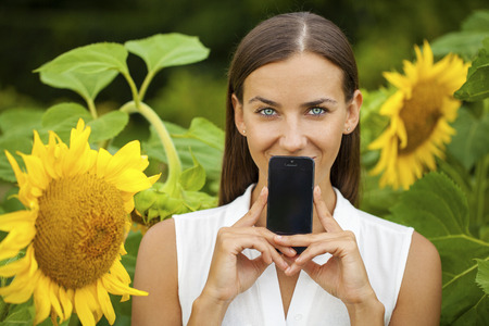 Young beautiful brunette woman showing your smartphone screen, summer park outdoors Stock Photo