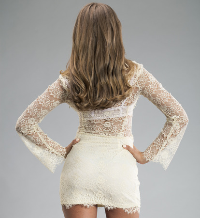 Young blonde woman in a cocktail dress, rear view, on a gray background. Studio shot