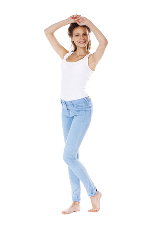 18's: Happy brunette girl in white t-shirt and blue jeans, isolated on white background Stock Photo