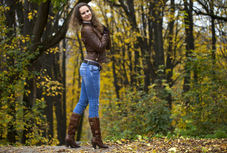 leather gloves: Autumn fashion image of young woman walking in the park, wearing leather jacket and blue jeans