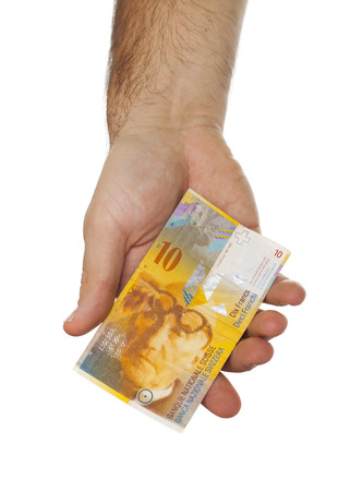 arms trade: Man hand giving 10 swiss franc banknote isolated on white background Stock Photo