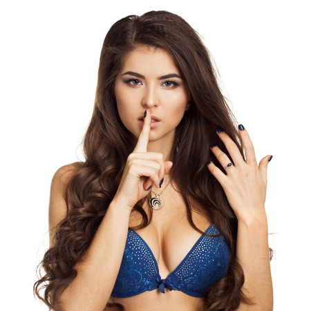 requires: Woman requires silence. Young beautiful brunette has put forefinger to lips as sign of silence, isolated on white Stock Photo