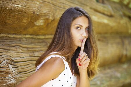 Young beautiful brunette woman has put forefinger to lips as sign of silence, against green summer garden Stock Photo