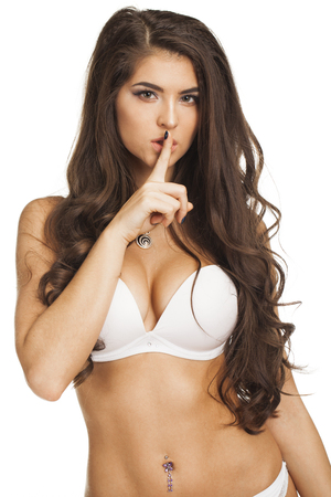 Woman requires silence. Young beautiful brunette has put forefinger to lips as sign of silence, isolated on white Stock Photo