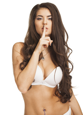 shushing: Woman requires silence. Young beautiful brunette has put forefinger to lips as sign of silence, isolated on white Stock Photo