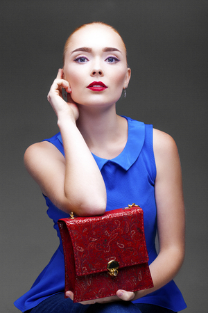 designer bag: Beautiful fashion sexy blonde woman with bright makeup posing at studio isolated on gray background Stock Photo