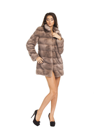 Portrait in full growth on a beautiful brunette woman short mink coat, isolated on white background Stock Photo