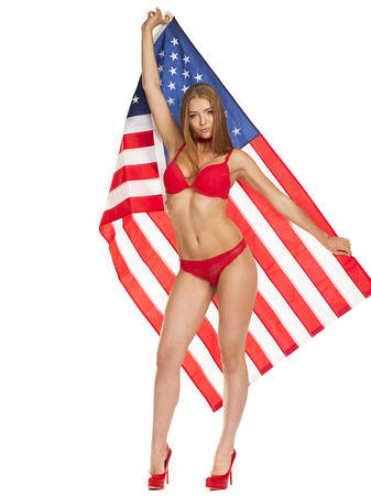 Beautiful blonde woman in red bikini holding the USA flag. Isolated on white background