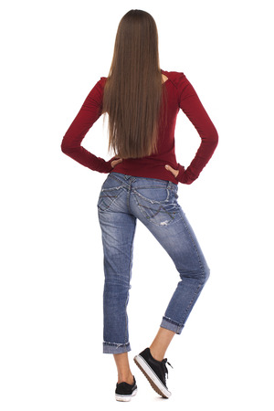 Back view. Brunette woman in blue jeans and red jacket, isolated on white background