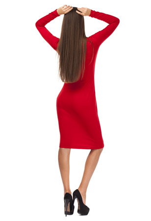 Portrait in full growth of a beautiful young woman in red dress, isolated on white background