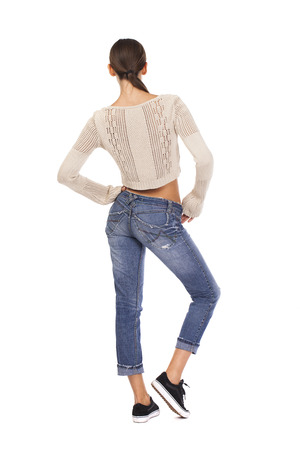 knitted jacket: Happy brunette woman in blue jeans and knitted jacket, isolated on white background