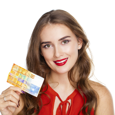 Young happy brunette woman holds a 10 Swiss francs, isolated on white background. Suisse francs bank note. Suisse franc is the national currency of Switzerland Stock Photo