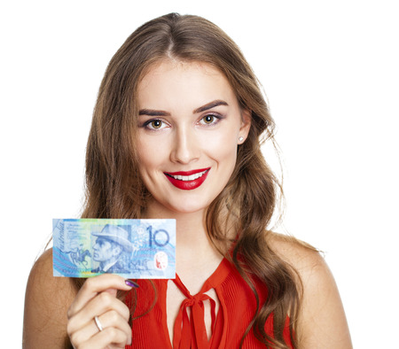 shushing: Young happy brunette woman holds 10 Australian dollar Banknote. Isolated on white Stock Photo