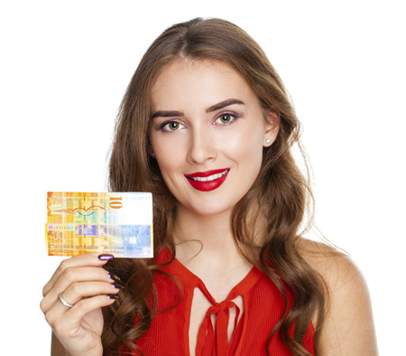 shushing: Young happy brunette woman holds a 10 Swiss francs, isolated on white background. Suisse francs bank note. Suisse franc is the national currency of Switzerland Stock Photo