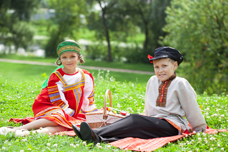 Two happy children in russian folk clothes on green grass