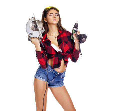 Young sexy brunette woman holding a construction drill