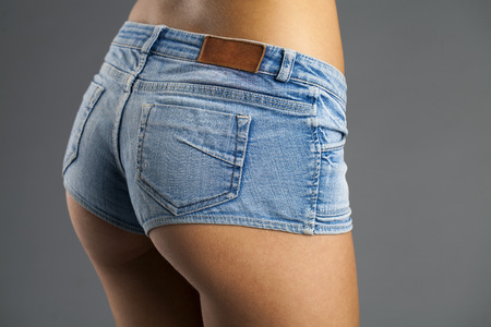 Back View. Sexy woman in fashion blue jeans shorts. Perfect hot booty and erotic curves hips. isolated on gray background