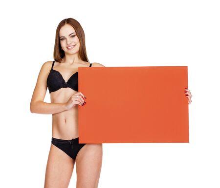 busty: La mujer joven atractiva morena en ropa interior negro que sostiene la bandera roja, aislado en fondo blanco Foto de archivo