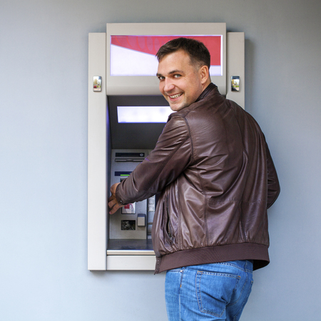 withdrawing: Young happy brunette man withdrawing money from credit card at ATM