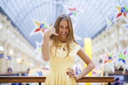 call me: Call Me. Young beautiful blonde woman in yellow dress, posing against a background of a New Years interior