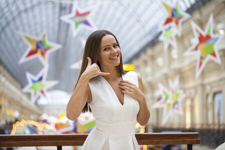 call me: Call Me. Young beautiful brunette woman in white dress, posing against a background of a New Years interior