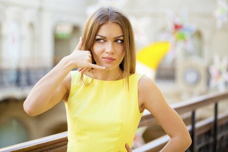 Call Me. Young beautiful blonde woman in yellow dress, posing against a background of a New Years interior