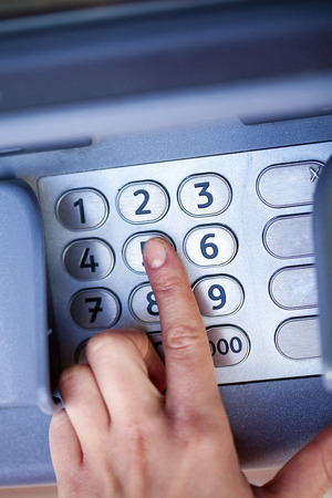 personal identification number: Close up of hand entering pin at an ATM. Finger about to press a pin code on a pad. Security code on an Automated Teller Machine. Female arms, ATM - entering pin