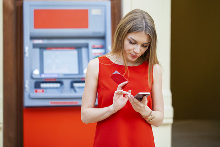 Young happy woman шт red dress withdrawing money from credit card at ATM  Stock Photo