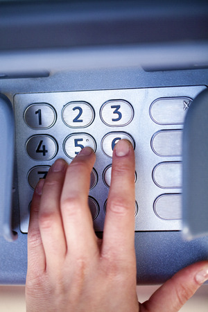 pin code: Close up of hand entering pin at an ATM. Finger about to press a pin code on a pad. Security code on an Automated Teller Machine. Female arms, ATM - entering pin