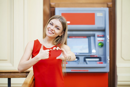 cash slips: Young happy blonde woman in red dress withdrawing money from credit card at ATM