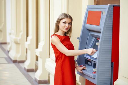 ATM でクレジット カードからお金を引き出す赤いドレスの若い幸せなブロンドの女性