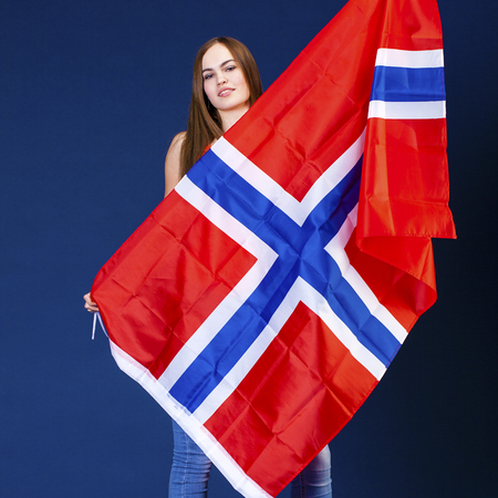 Young beautiful girl holding a large flag of Norway, dark blue studio Stock Photo