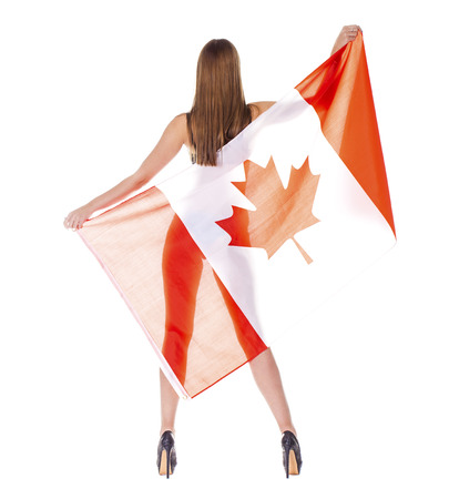 Young beautiful woman holding a large Canadian flag transparent, isolated on white background