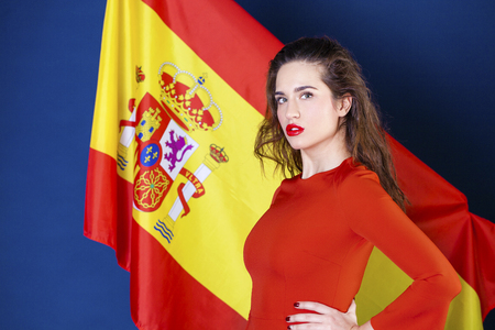 Young beautiful brunette woman on the background of the Spanish flag