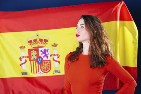yellow teeth: Young beautiful brunette woman on the background of the Spanish flag