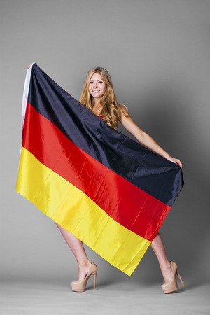 Young beautiful woman holds up a clear flag of Germany