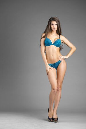 isolated on gray: Full length portrait of young brunette model wearing blue underwear, isolated on gray background