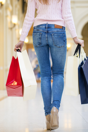 Young beautiful woman with some shopping bags walking in the mall